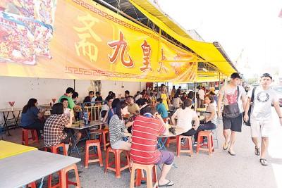街边临时素食档口旁坐满用餐的善信们。