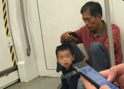 男子不愿弄污地铁座位将外套脱下垫在地上给孩子坐。