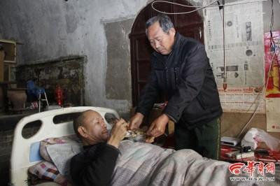 崔申旺多年来风雨不改,坚持照顾与他非亲非故的瘫痪男子尹买旺。