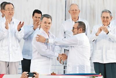 桑托斯(眼前左)以及叛军领袖隆多尼奥(眼前右)上月签署和平协议,联合国秘书长潘基文(左)和古巴总统劳尔(右)见证。