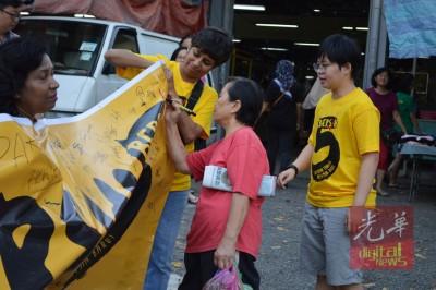 益美园巴刹民众在横幅上签名支持。