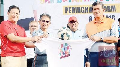 阿斯里(右)于体育日上移交T恤及足球予吉州警方刑事调查组主任纳希尔与行政长官阿兹春秋(左)。