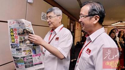 马袖强(左)阅读《光华日报》,观看之前民政党元老会议的报道。旁为刘华才。