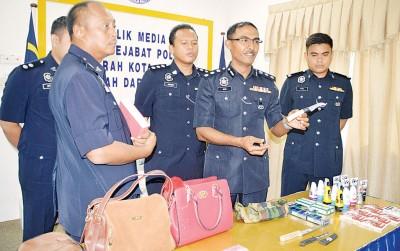 罗兹(右2)在一众调查警官的陪同下,出示匪党在便利商店抢劫所使用的武器。