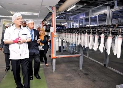 马袖强(左)每当林伟才之指引下,浏览顶级手套在实达阿南的研发室。