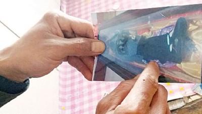 小英丈夫展示妻子遗体的照片。