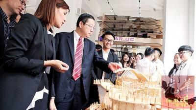 陈美佑(左起)陪同林冠英巡视学生建筑设计作品。