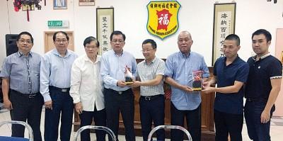 骆南辉(左4)在梁宗宝(左3)及陈来福(右3)的陪同下,赠送纪念品给陈忠坤(左5)。