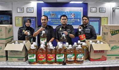 莫哈末法里(右2)及官员们展示所充公的食油。