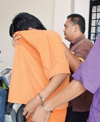 嫌犯离开法庭时,拉起衣服遮脸,避开摄记的镜头。