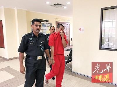 被告黄益达(译音)被狱警带出法庭时,以衣服遮盖脸部。