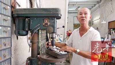 薛美祥借机器进行手工制作广告牌。