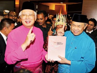 """纳吉(左)与阿末扎希向媒体展示2017年财政预算案建议书,竖起""""一个马来西亚""""手势。"""