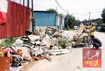 居民以三轮车载已损坏的地毯等丢在路边,等候垃圾车前来收拾。