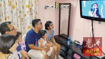 佩玲的家人在住家电视前,全神贯注观看佩玲表演。
