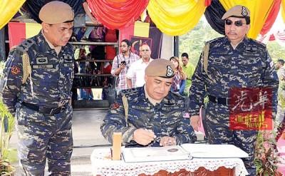 卡立(左2)抵达乌鲁近打普通行动部队(北旅)基地后在纪念册上签名留念,右2为莫哈末沙都。