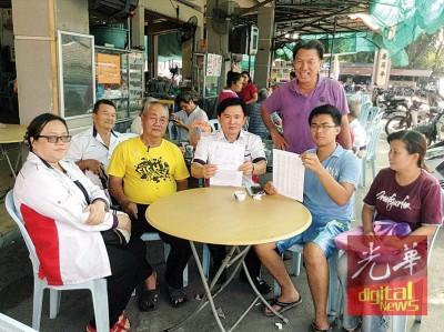 杨祖强(中)与事主何家荣(右2)展示报案书及银行户头进支纪录。
