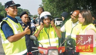 陈佩红(左)通告赠小礼袋予交通使用者。