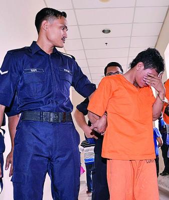 疑犯周三被带到法庭申请延长拘留后,离开法庭时用手遮脸。