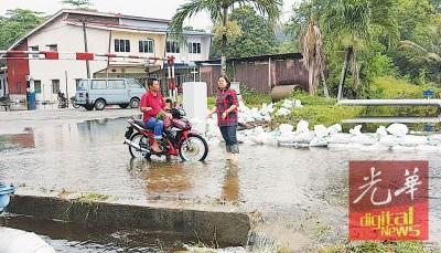 蔡依霖水中向农民了解淹水情况。