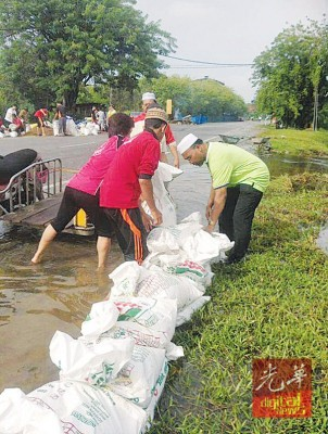 武吉干当区国会议员依德利斯(右)为和老百姓联合准备沙包筑堤。