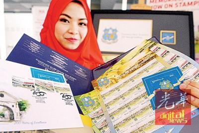邮政公司女员工展示即将本周五发行的大英义学首日封及明信片。