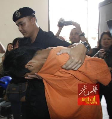 男嫌犯被押上法庭时,全程低头以拉起衣服遮脸。