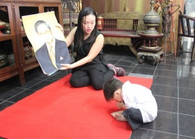小达(右)唱歌后,跪拜泰王。(互联网图片)