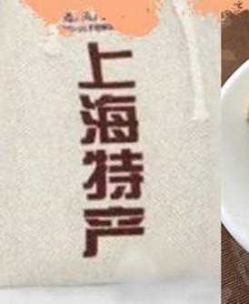 """""""狗屎糕""""以麻布袋装着,包装外印上""""上海特产""""大字。"""