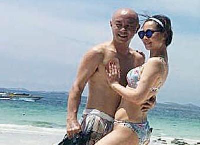 张卫健及夫人在沙滩上拍照。