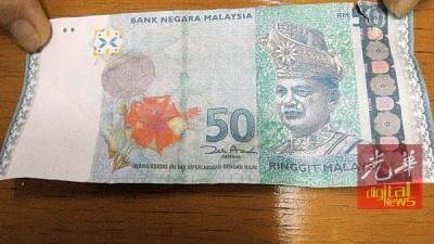 贾包小贩收到的50令吉假钞,正当大红花已脱色,右的条纹也没闪亮。