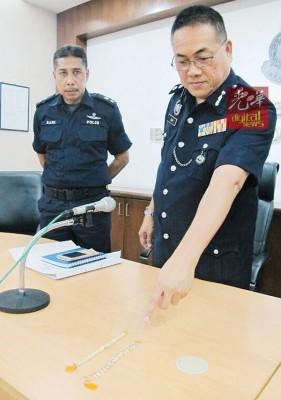 岑振强(右)在记者会上展示警方起获的2条手链,左为拉尼。