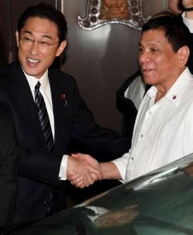 岸田文雄(左)与迪泰特(右)握手。(法新社照片)