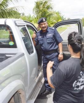 阿兹占(左)与执法员一同检查入境我国的泰国车牌货车,也向司机了解去处。