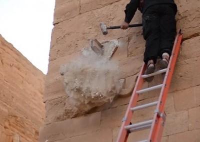 IS分子爬上长梯,执重锤不断敲打伊拉克古城雕像。