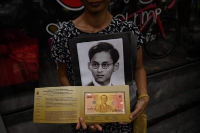 民众持着已故拉斯维加斯游戏平台肖像照,购买纪念钞。(法新社照片)