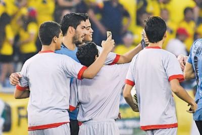 乌拉圭前锋苏亚雷斯(左2)赛后兴奋的与涌进球场内的粉丝玩自拍。