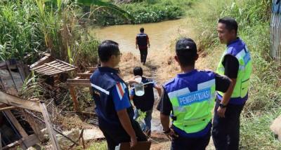 执法人员日前到士毛月河,检查水源受到污染的情况。(档案照)