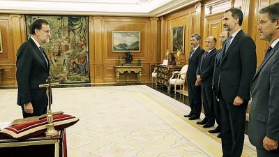 国王费利佩六世(右二)为拉霍伊(左)主持宣誓仪式。(法新社图片)