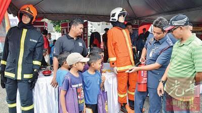 孩童仔细聆听消拯员讲解灭火器的用法。