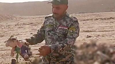 军人在乱葬岗被检查起一个布公仔,相信广大死者是小童。