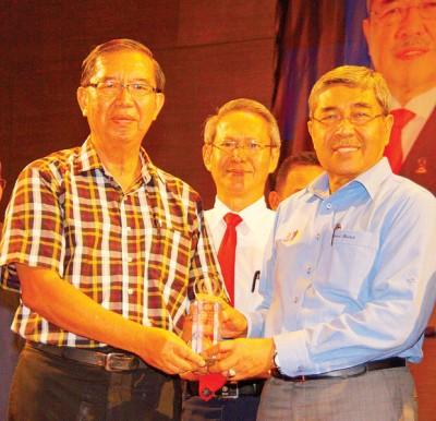 华校资深教师伍国赐从大臣手中接领奖杯,中为梁荣光。