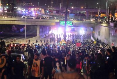 洛杉矶大批示威者堵塞101承担李活高速公路,以及派出所对峙。(法新社照片)