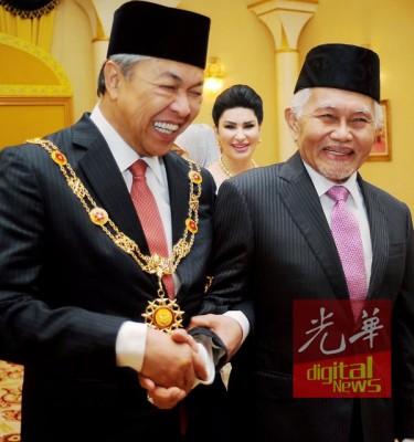 """泰益玛望(右)和阿末扎希握手,贺后者获授""""拿督巴丁正好""""勋衔,继也州元首后杜潘拉嘉古迪平静益。"""