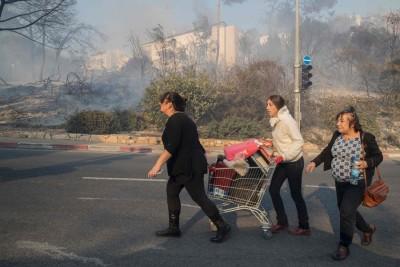 起居民拿家当装到超市手推车,推动着逃离家园。(法新社照片)