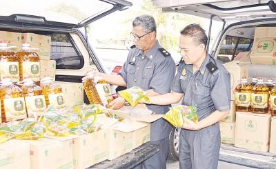 萨玛(左)与执法员展示遭充公的罐装与包装的食油。