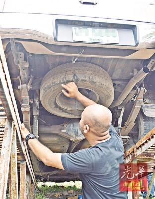 执法人员向媒体示出藏在车底下的改装油箱。