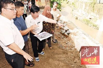 曹观友在黄汉伟陪同下与居民杨文明了解河岸抢修工程进展。