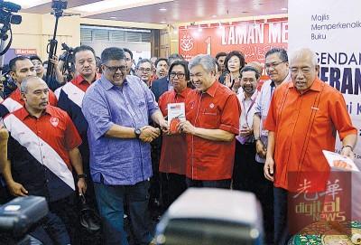 阿末扎希(前排右2起)在执行秘书拿督阿都劳勿和最高理事拿督斯里马哈基尔卡立(右1)等人见证下,推介新书。
