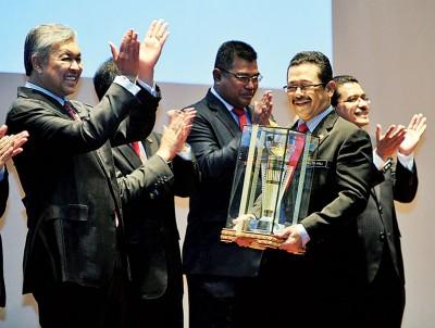 """阿末扎希(左)通告内政部革新日的""""内政部长杯""""于大马监狱局,由于监狱局总监拿督斯里祖基菲里代表接领。"""